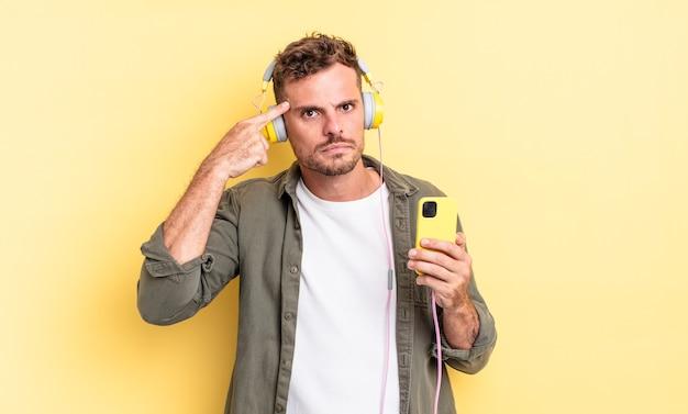 Junger gutaussehender mann, der sich verwirrt und verwirrt fühlt und zeigt, dass sie verrückte kopfhörer und smartphone-konzept sind