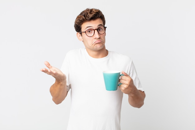 Junger gutaussehender mann, der sich verwirrt und verwirrt fühlt und zweifelt und eine kaffeetasse hält