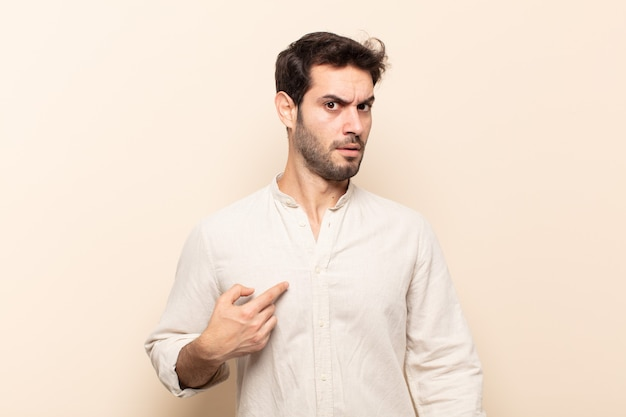 Junger gutaussehender mann, der sich verwirrt, verwirrt und unsicher fühlt, auf selbstwunder zeigt und fragt, wer, ich?