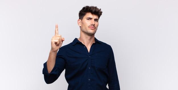 Junger gutaussehender mann, der sich wie ein genie fühlt, das stolz finger in der luft hält, nachdem er eine große idee verwirklicht und eureka sagt