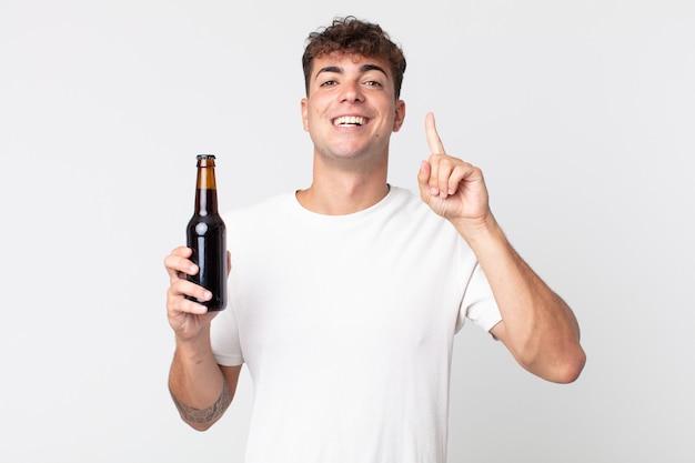Junger gutaussehender mann, der sich wie ein glückliches und aufgeregtes genie fühlt, nachdem er eine idee realisiert und eine bierflasche hält
