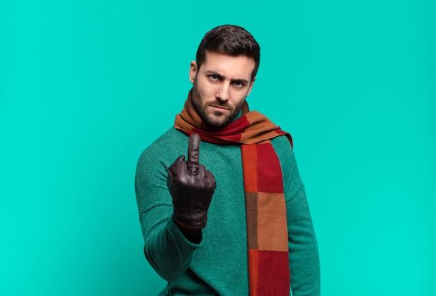 Junger gutaussehender mann, der sich wütend, verärgert, rebellisch und aggressiv fühlt, den mittelfinger dreht und sich wehrt. kälte- und winterkonzep