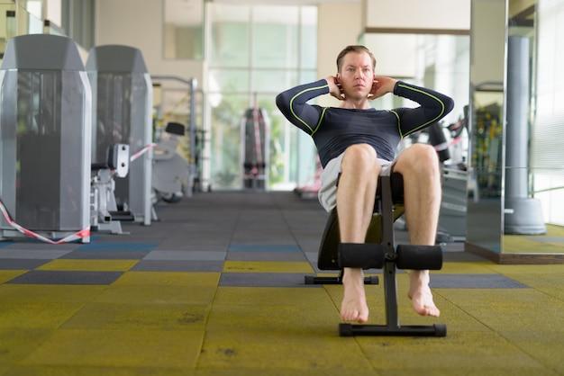Junger gutaussehender mann, der sit-ups im fitnessstudio während covid-19 macht