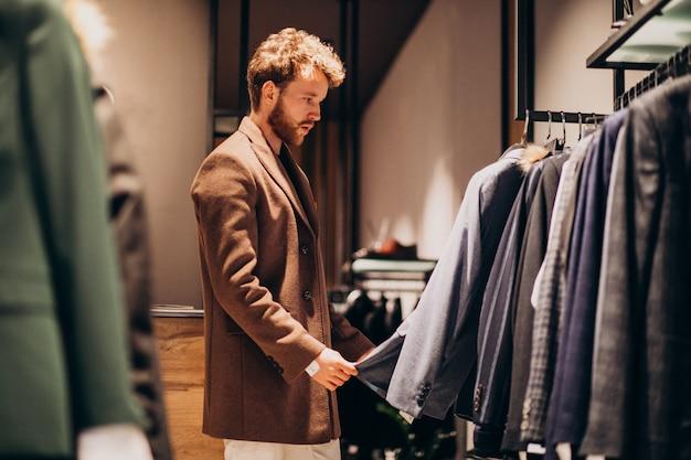 Junger gutaussehender mann, der stoff am shop wählt