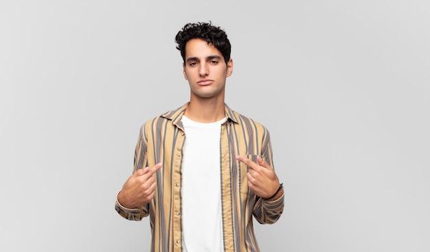 Junger gutaussehender mann, der stolz, positiv und lässig aussieht und mit beiden händen auf die brust zeigt