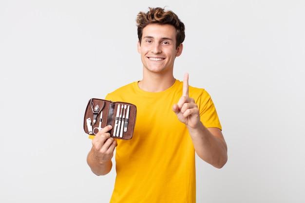 Junger gutaussehender mann, der stolz und selbstbewusst lächelt, die nummer eins macht und einen nagelwerkzeugkoffer hält