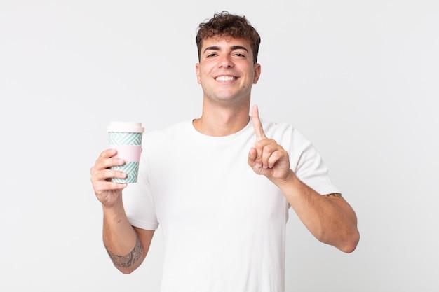 Junger gutaussehender mann, der stolz und selbstbewusst lächelt, nummer eins macht und einen kaffee zum mitnehmen hält