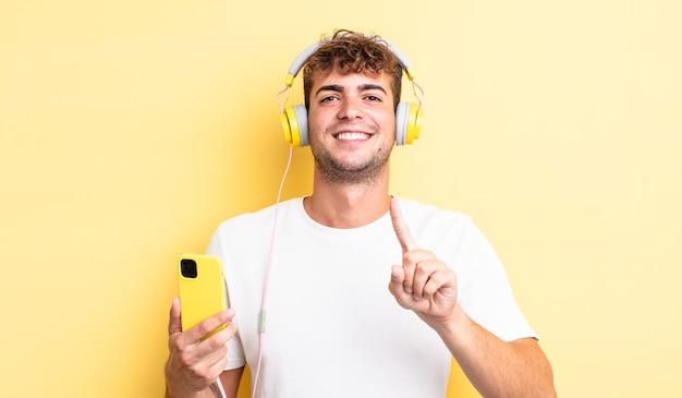 Junger gutaussehender mann, der stolz und selbstbewusst lächelt und die nummer eins macht. kopfhörer- und smartphone-konzept