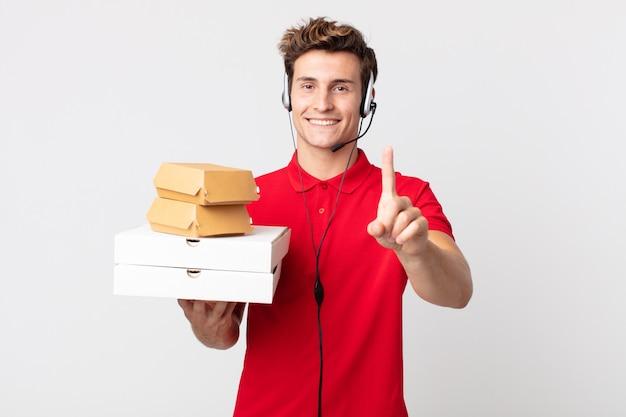 Junger gutaussehender mann, der stolz und selbstbewusst lächelt und die nummer eins macht. take-away-fast-food-konzept