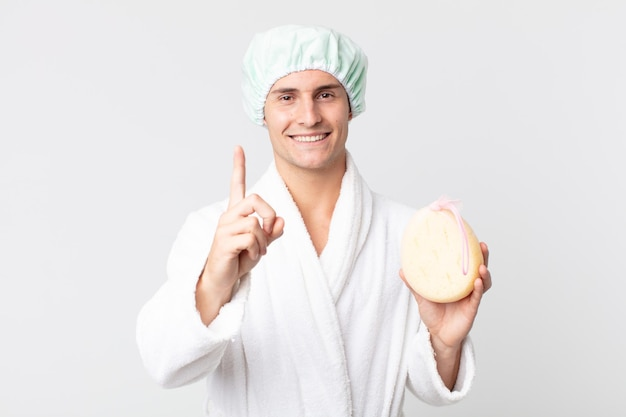 Junger gutaussehender mann, der stolz und selbstbewusst lächelt und die nummer eins mit bademantel, duschhaube und einem schwamm macht