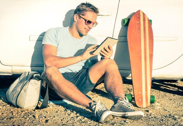 Junger gutaussehender mann, der tablette sitzt auf pause am straßenausflugabenteuer