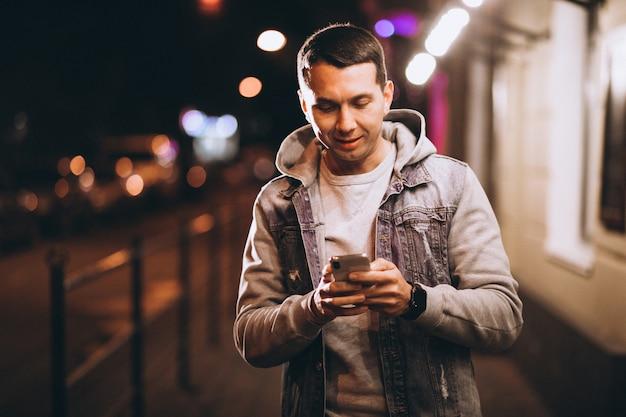 Junger gutaussehender mann, der telefon nachts in der straße verwendet