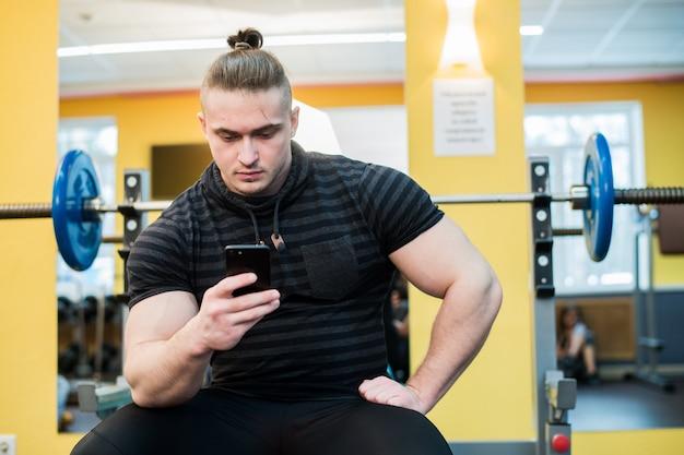 Junger gutaussehender mann, der telefon während der übungspause im fitnessstudio verwendet.