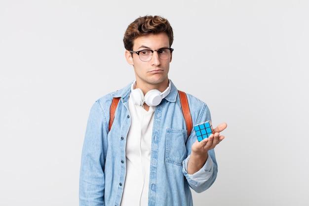 Junger gutaussehender mann, der traurig, verärgert oder wütend ist und zur seite schaut. intelligenzspielkonzept