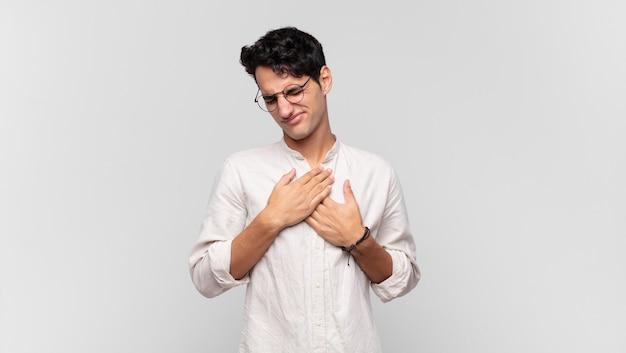 Junger gutaussehender mann, der traurig, verletzt und mit gebrochenem herzen aussieht, beide hände nah am herzen hält, weint und sich depressiv fühlt