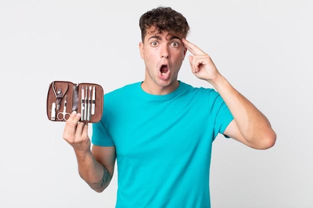 Junger gutaussehender mann, der überrascht aussieht, einen neuen gedanken, eine neue idee oder ein neues konzept realisiert und einen nagelwerkzeugkoffer hält