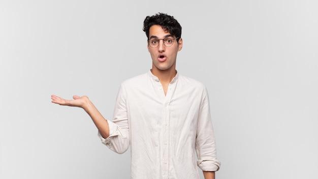 Junger gutaussehender mann, der überrascht und schockiert aussieht, mit gesenktem kiefer, der einen gegenstand mit einer offenen hand auf der seite hält