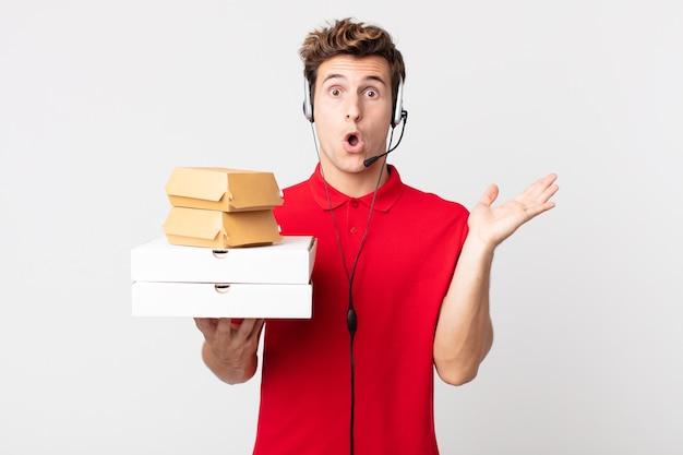 Junger gutaussehender mann, der überrascht und schockiert aussieht, mit heruntergefallenem kiefer, der einen gegenstand hält. take-away-fast-food-konzept