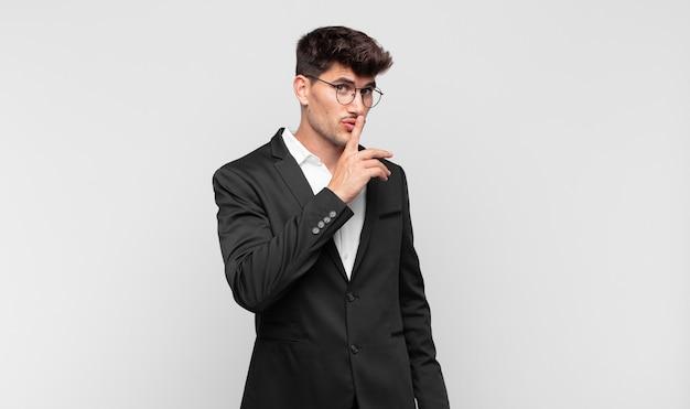 Junger gutaussehender mann, der um stille und ruhe bittet, mit dem finger vor dem mund gestikuliert, shh sagt oder ein geheimnis bewahrt