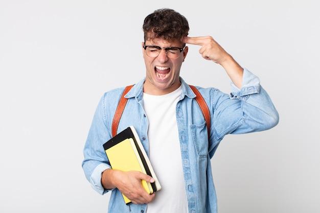 Junger gutaussehender mann, der unglücklich und gestresst aussieht, selbstmordgeste, die waffenzeichen macht. konzept für universitätsstudenten