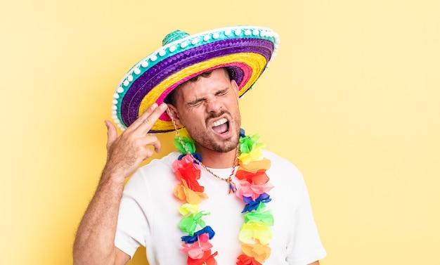 Junger gutaussehender mann, der unglücklich und gestresst aussieht, selbstmordgeste, die waffenzeichen macht. mexikanisches partykonzept