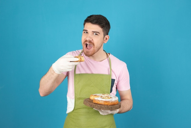 Junger gutaussehender mann, der versucht, kuchenscheibe auf einem blau zu beißen.