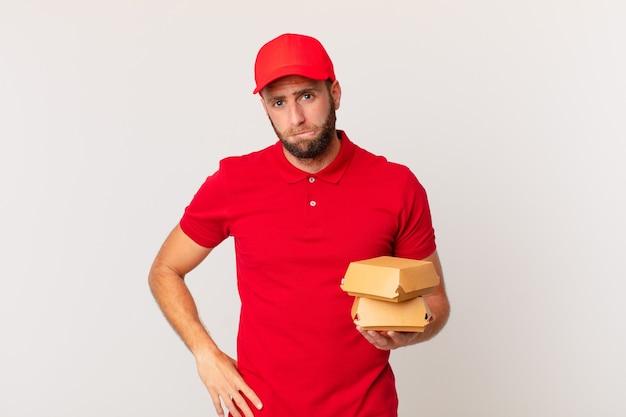 Junger gutaussehender mann, der verwirrt und verwirrt aussieht, burger liefert konzept