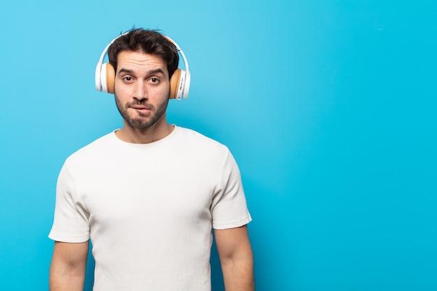 Junger gutaussehender mann, der verwirrt und verwirrt aussieht, mit einer nervösen geste auf die lippe beißt und die antwort auf das problem nicht kennt