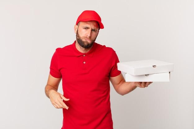 Junger gutaussehender mann, der verwirrt und verwirrt aussieht. pizza lieferkonzept