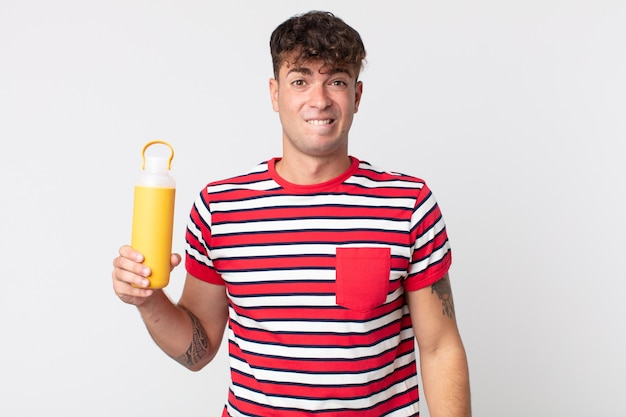 Junger gutaussehender mann, der verwirrt und verwirrt aussieht und eine kaffee-thermoskanne hält