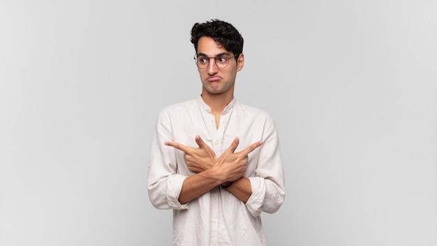 Junger gutaussehender mann, der verwirrt und verwirrt aussieht, unsicher ist und mit zweifeln in entgegengesetzte richtungen zeigt