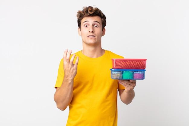Junger gutaussehender mann, der verzweifelt, frustriert und gestresst aussieht und lunchpakete hält