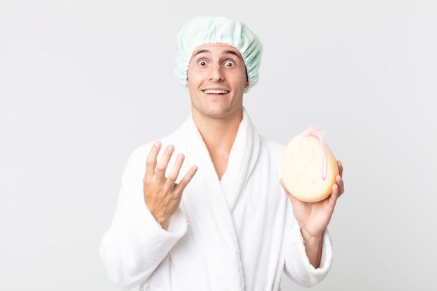 Junger gutaussehender mann, der verzweifelt, frustriert und gestresst mit bademantel, duschhaube und einem schwamm aussieht
