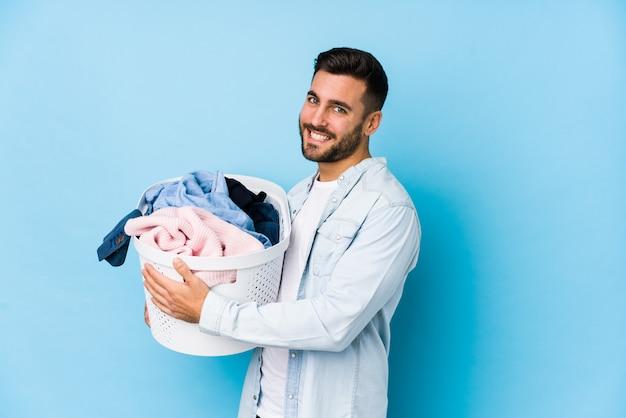 Junger gutaussehender mann, der wäsche isoliert tut, schaut lächelnd, fröhlich und angenehm beiseite.