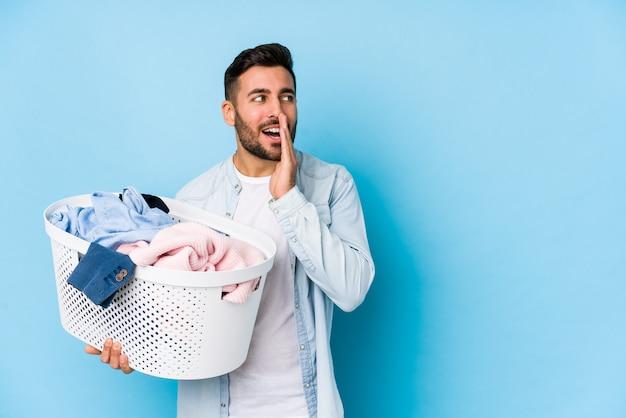 Junger gutaussehender mann, der wäsche macht, sagt eine geheime heiße bremsnachricht und schaut zur seite