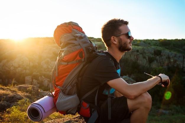 Junger gutaussehender mann, der walkie-talkie-radio hält und canyonblick genießt