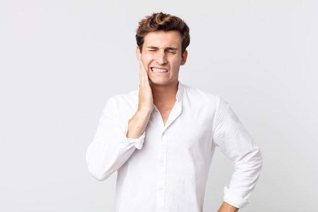 Junger gutaussehender mann, der wange hält und schmerzhafte zahnschmerzen hat, sich krank, elend und unglücklich fühlt, auf der suche nach einem zahnarzt