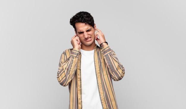 Junger gutaussehender mann, der wütend, gestresst und genervt aussieht und beide ohren zu einem ohrenbetäubenden geräusch, ton oder laute musik bedeckt