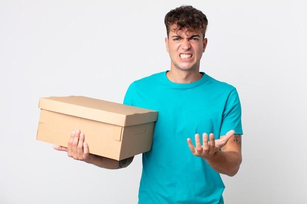 Junger gutaussehender mann, der wütend, verärgert und frustriert aussieht und einen karton hält