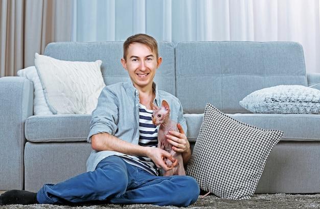 Junger gutaussehender mann, der zu hause mit katze auf dem boden sitzt Premium Fotos