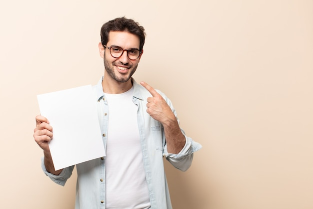 Junger gutaussehender mann, der zuversichtlich lächelt und auf eigenes breites lächeln, positive, entspannte, zufriedene haltung zeigt