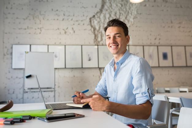 Junger gutaussehender mann des glücklichen entfernten arbeiters, der denkt, notizen in notizbuch schreibt