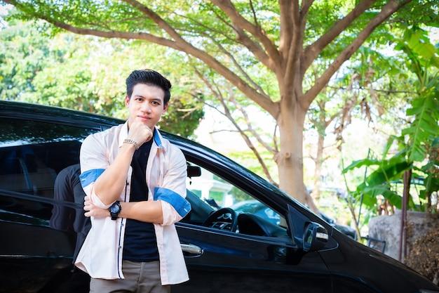 Junger gutaussehender mann des porträts warf stellung mit auto auf