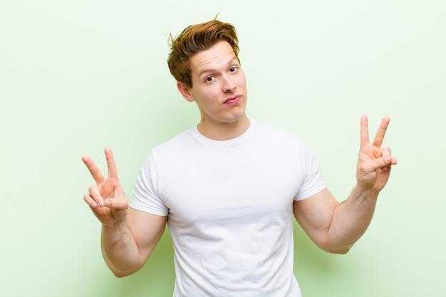 Junger gutaussehender mann des roten kopfes, der lächelt und glücklich, freundlich und zufrieden schaut und sieg oder frieden mit beiden händen gestikuliert
