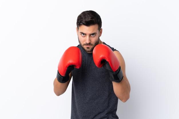 Junger gutaussehender mann des sports mit bart über weiß mit boxhandschuhen