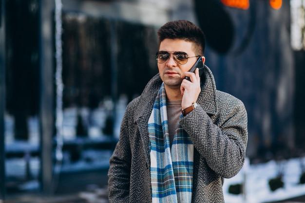 Junger gutaussehender mann draußen unter verwendung des telefons