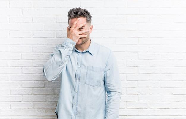 Junger gutaussehender mann gegen backsteinmauer blinzelt durch finger, verlegenes bedeckendes gesicht