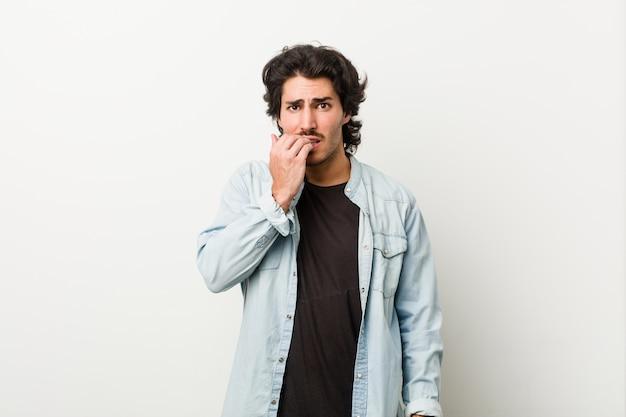 Junger gutaussehender mann gegen beißende fingernägel eines weißen hintergrundes, nervös und sehr besorgt.