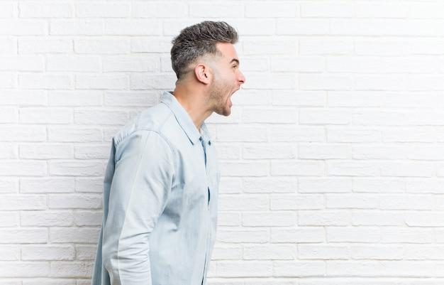 Junger gutaussehender mann gegen eine ziegelsteinwand schreiend in richtung zu einem kopienraum