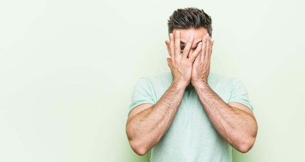 Junger gutaussehender mann gegen einen grünen hintergrundblinken durch die finger erschrocken und nervös.